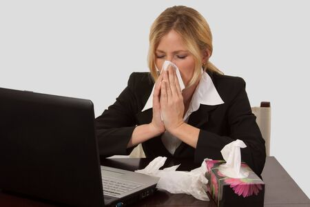 Blond caucasian woman wearing business attire sitting in front of laptop computer with a box of tissues blowing her nose photo