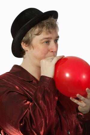 Short hair blond caucasian middle-age woman wearing a black party hat blowing up a red balloon  Imagens