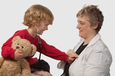 Young caucasian boy and a short hair woman in medical doctor uniform holding a stethoscope on his ear listening to doctor heart beat holding a brown teddy bear photo