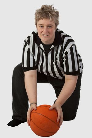 Short hair blond mother type woman wearing striped referee shirt holding a basketball over white Imagens