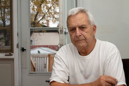 indoors: Sad looking senior caucasian man sitting indoors