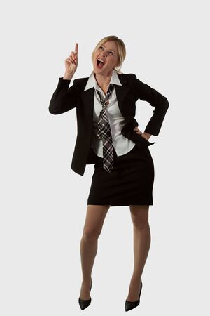 Full body of an attractive blond woman wearing business suit with tie and skirt looking and pointing up with mouth open