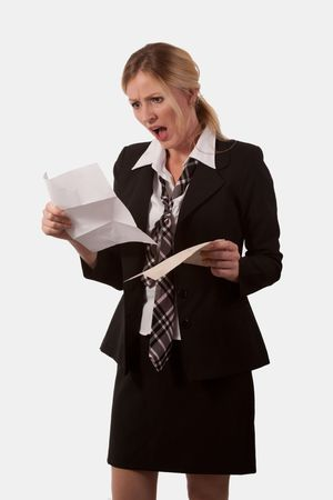 Attractive blond caucasian woman wearing a black business suit with tie holding an open envelope and a letter staring at it with an angry shocked expression