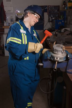 vice grip: Woman mechanic working in a workshop using a vice grip hammering