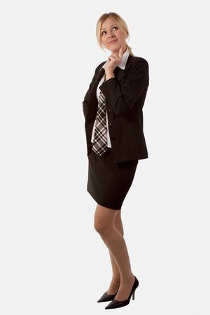 thinking woman: Full body of attractive blond woman with long legs wearing business suit skirt and tie standing on white with hand on chin looking up thinking