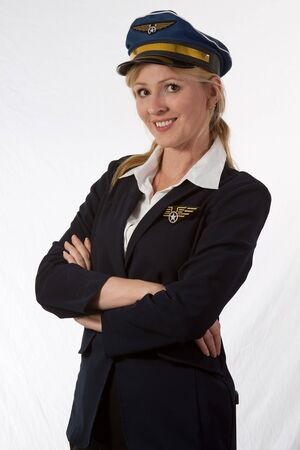 Pretty blond woman pilot with arms crossed wearing hat