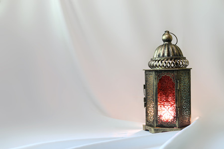 Ancient colored lantern on white satin