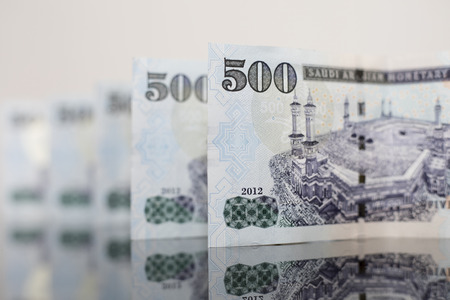 aligned Saudi Notes on a dark glass