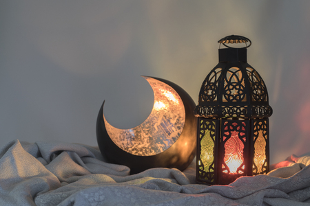 Lantern and a copper crescent shape on a satin cloth