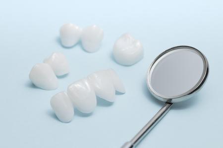 Dental mirror and zircon dentures on a light blue background Banco de Imagens