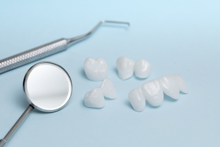 Dental tools and zircon dentures on a light blue background