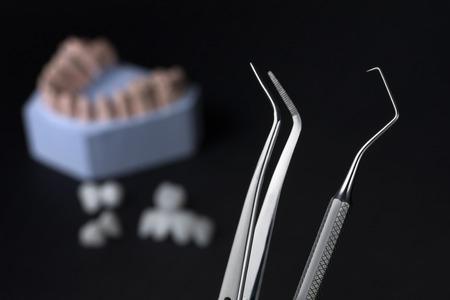 Dental tools with zircon dentures on a black background - Ceramic veneers - lumineers Banco de Imagens