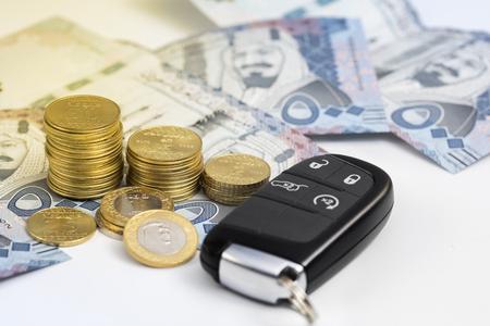 Saudi riyal coins and key of car, expresses the car insurance,finance and buying car. Banco de Imagens