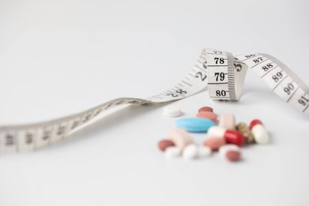 Measuring tape with some medicines, the photo express the diet and nutrition
