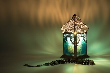 Lantern with Rosary beads reflect colored light on background