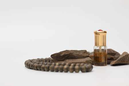 Bottle of oil agarwood  with Incense Chips isolated on white background