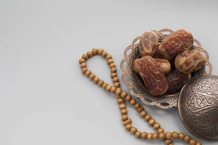 Dates fruits on a copper bowl with rosary beads on a gray background