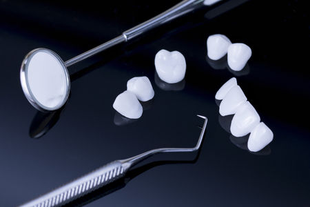 Dental tools and Tooth implant on a black reflection surface