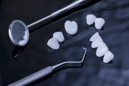 Close up dental tools and Tooth implant on a black reflection surface
