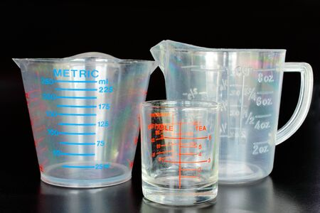 Measuring cups on the black background photo