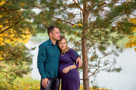 Loving couple in autumn Park. Pregnancy Stock Photo