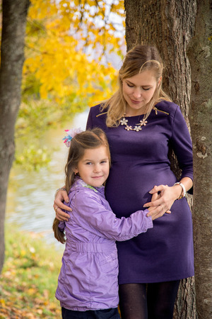 Pregnant mother with daughter on walk at autumn Park Stock Photo