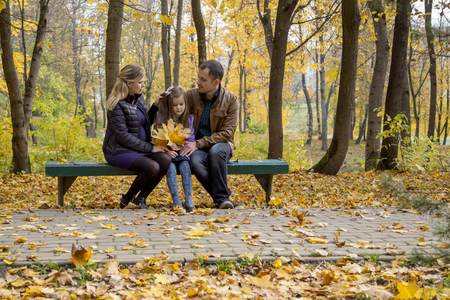 Happy pregnant family in autumn nature Stock Photo