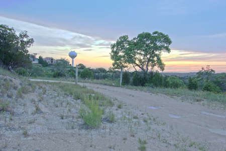 the water tower: Dirt road at dusk with water tower in background Stock Photo