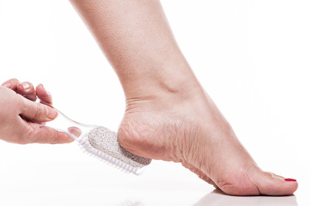 care for dry skin on the well-groomed feet and heels with the help of tools pedicure pumice and brush Foot.
