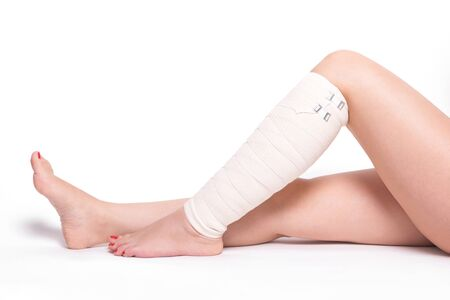 sprained joint: ankle woman on a white background dragged elastic bandage. Stock Photo