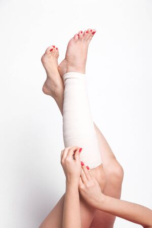 sprained joint: girl on a white background corrects an elastic bandage which tied her leg.