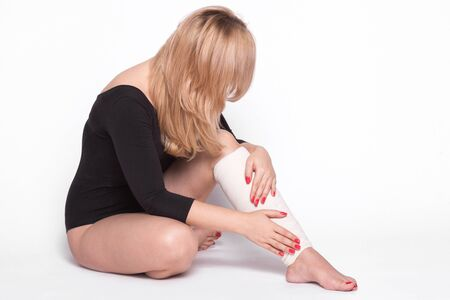 tied girl: girl on a white background corrects an elastic bandage which tied her leg.