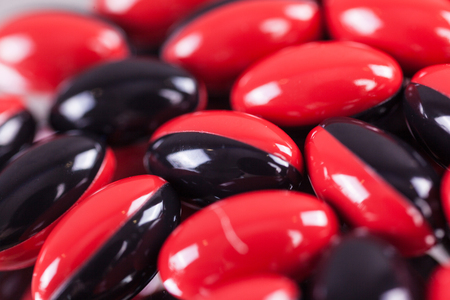 a scattering of red-black brown pills on the mirror background, macro, picture with depth of field