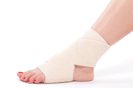 sprained joint: studio shot female ankle tied with an elastic bandage.