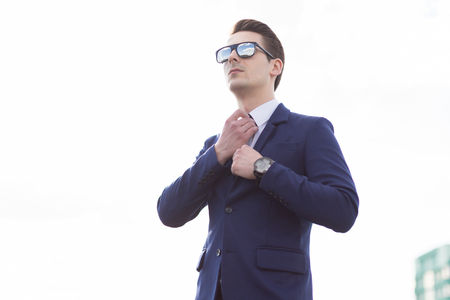 cheer full: Young businessman with glasses on the roof Stock Photo