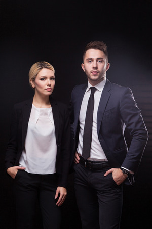 advocates: stylish, trendy and modern business man and woman on black background looking confidently at the camera