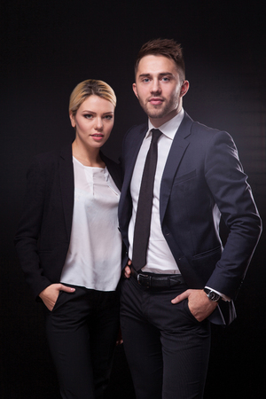 advocates: stylish, trendy and modern business man and woman on black background looking confidently at the camera.