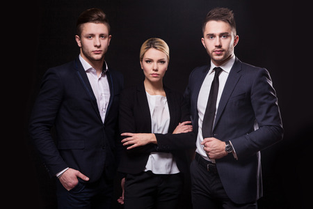 advocates: Team of three successful stylish young lawyers on a black background, a woman and two men businessmen Stock Photo