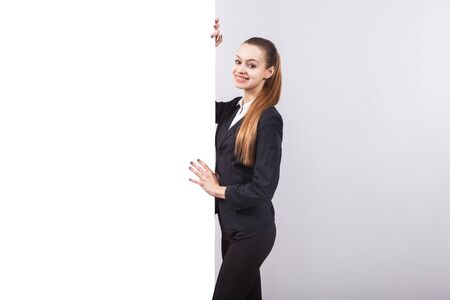 promotes: Young successful business woman standing next to a whiteboard on white background and promotes creative product