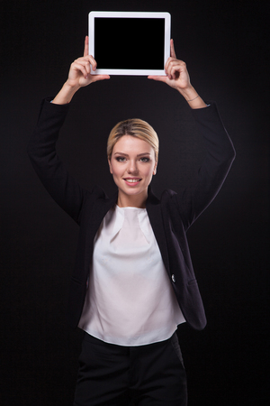 arms above head: successful young businessman woman in a stylish black business suit and a white blouse on a black background confident holding at arms length above the head tablet display forward and smiling. Stock Photo