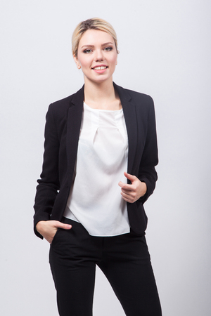 Business lady blonde in black stylish suit standing on a white background and smiling