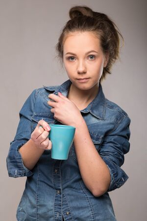 lethargy: sleepy student with a cup of coffee in hand on studio background
