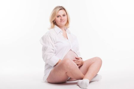 pregnant blonde: Pregnant blonde woman in white shirt sitting cross-legged on a white background holding his stomach and looks into the camera with a smile