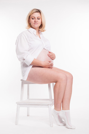 pregnant blonde: pregnant blonde in white shirt and white socks sitting on a stool on a white background and holding her stomach