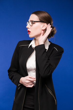 caras emociones: young brunette woman in a jacket with red lipstick on a blue background Foto de archivo