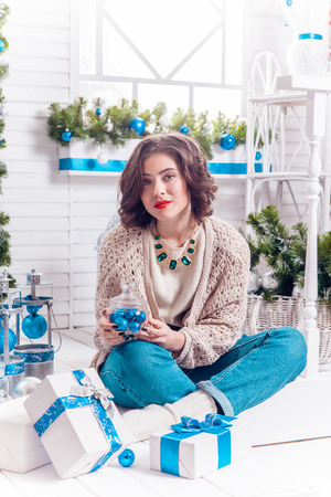 sexy beautiful woman sits near a Christmas tree dressed up in Christmas balls with gifts in their hands, picture with depth of field Stock Photo