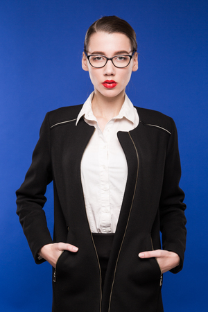 woman in a dark jacket with a red lipstick with glasses on a blue background Stock Photo