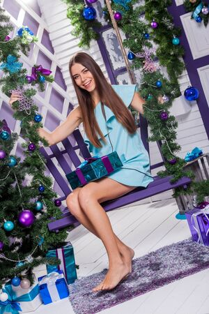 merrymaking: brunette in a turquoise dress sitting on a swing next to a Christmas tree decorated with purple and blue balloons and holding a gift. Stock Photo