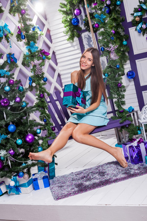 miracle tree: brunette in a turquoise dress sitting on a swing next to a Christmas tree decorated with purple and blue balloons and holding a gift. Stock Photo