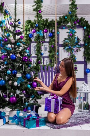 merrymaking: leggy brunette in a turquoise dress sitting on a purple swing on the terrace surrounded by a Christmas tree with baubles and gifts smiling and looking at the camera. Stock Photo